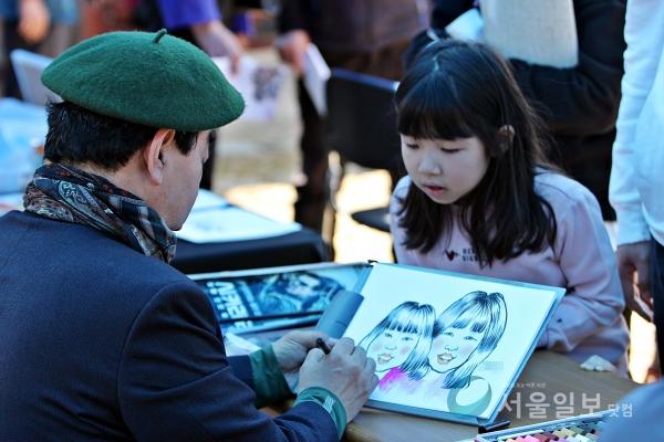 한 어린이가 자신을 그린 캐리커처가 궁금한 듯 그림을 보려고 하고 있다.(사진=송승화 기자)